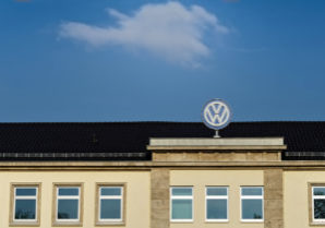 Brunswick, Lower Saxony, Germany - April 15, 2018: Upper part of the Volkswagen administration building with a large VW logo and lot of space above in the sky with a cloud