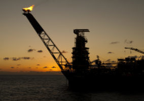 Silhouette of an FPSO oil rig bow at sunset/sunrise time, with flare burning gas.